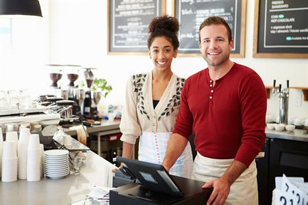 Photograph of a woman and a man working in a coffee shop.